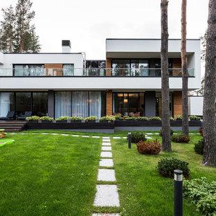 На фото: двухэтажный, белый частный загородный дом в современном стиле с плоской крышей с