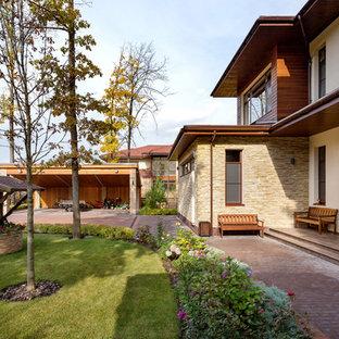 Modelo de fachada de casa beige, ecléctica, grande, de dos plantas, con revestimientos combinados, tejado plano y tejado de teja de madera