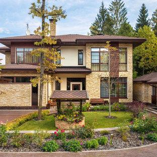 На фото: бежевый, двухэтажный частный загородный дом в стиле фьюжн с комбинированной облицовкой и вальмовой крышей с