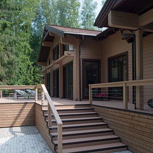 На фото: большой, одноэтажный фасад частного дома бежевого цвета в скандинавском стиле с облицовкой из дерева и крышей из гибкой черепицы с