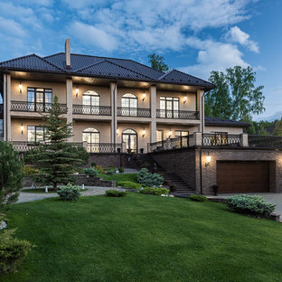 На фото: большой, двухэтажный, кирпичный, бежевый частный загородный дом в классическом стиле