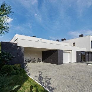 Пример оригинального дизайна: большой, белый частный загородный дом в современном стиле с разными уровнями, комбинированной облицовкой и плоской крышей
