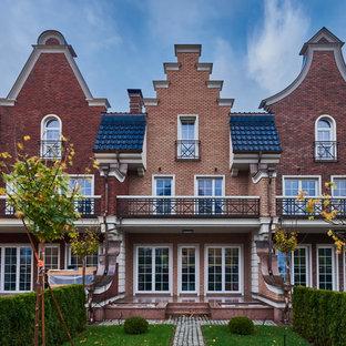 Создайте стильный интерьер: трехэтажный фасад таунхауса красного цвета в классическом стиле с облицовкой из кирпича - последний тренд
