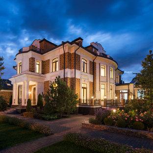 Неиссякаемый источник вдохновения для домашнего уюта: большой, трехэтажный, разноцветный фасад частного дома в классическом стиле с комбинированной облицовкой и металлической крышей