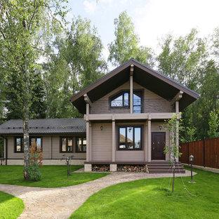 На фото: двухэтажный, деревянный, серый частный загородный дом среднего размера в стиле кантри с двускатной крышей с