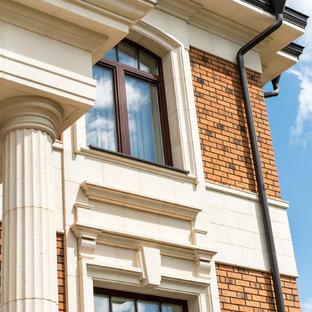 Imagen de fachada de casa multicolor, tradicional, grande, a niveles, con revestimiento de ladrillo, tejado a doble faldón y tejado de metal