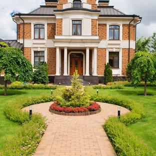 Diseño de fachada de casa multicolor, clásica, grande, a niveles, con revestimiento de ladrillo, tejado a doble faldón y tejado de metal