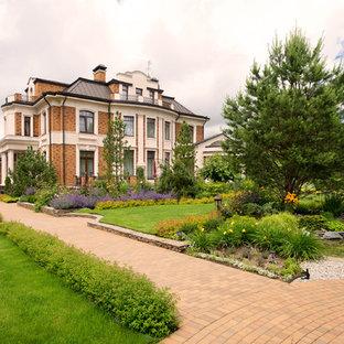 Modelo de fachada de casa multicolor, clásica, grande, a niveles, con revestimiento de ladrillo, tejado a doble faldón y tejado de metal