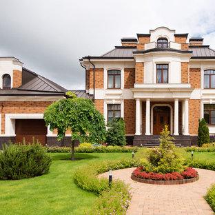 Новые идеи обустройства дома: большой, разноцветный фасад частного дома в классическом стиле с разными уровнями, облицовкой из кирпича, мансардной крышей и металлической крышей