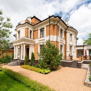 Diseño de fachada de casa multicolor, tradicional, grande, a niveles, con revestimiento de ladrillo, tejado a doble faldón y tejado de metal