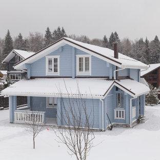 Пример оригинального дизайна интерьера: двухэтажный фасад частного дома синего цвета в скандинавском стиле с облицовкой из дерева и двускатной крышей