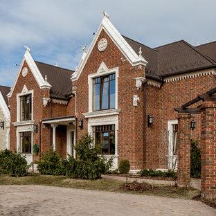 На фото: двухэтажный фасад частного дома коричневого цвета в викторианском стиле с облицовкой из кирпича с