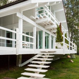 Imagen de fachada blanca, nórdica, de dos plantas, con revestimiento de madera y tejado a dos aguas