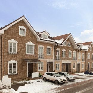 Новый формат декора квартиры: трехэтажный фасад таунхауса коричневого цвета в классическом стиле с облицовкой из кирпича и двускатной крышей