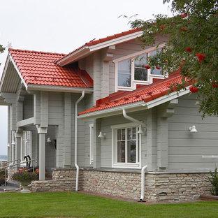 Неиссякаемый источник вдохновения для домашнего уюта: фасад частного дома серого цвета в современном стиле с облицовкой из дерева и двускатной крышей