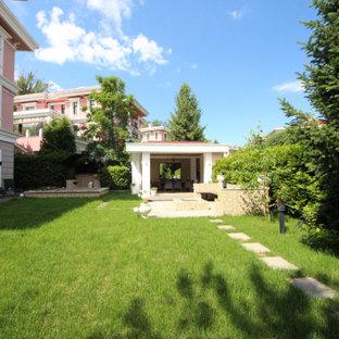 Ejemplo de fachada de casa rosa, ecléctica, grande, de tres plantas, con revestimientos combinados, tejado a dos aguas y tejado de teja de barro