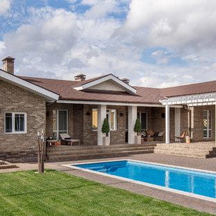 На фото: одноэтажный, кирпичный, коричневый частный загородный дом среднего размера в средиземноморском стиле с двускатной крышей и крышей из гибкой черепицы с