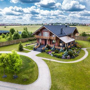 На фото: двухэтажный, кирпичный, красный частный загородный дом в стиле рустика с двускатной крышей и черепичной крышей