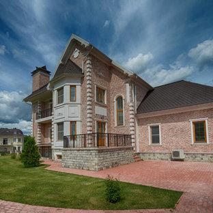 На фото: фасады домов коричневого цвета в классическом стиле с облицовкой из кирпича и двускатной крышей
