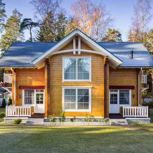 На фото: двухэтажные фасады дуплексов коричневого цвета в классическом стиле с облицовкой из дерева и двускатной крышей