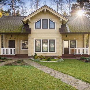 На фото: двухэтажный, деревянный, бежевый дуплекс в классическом стиле с двускатной крышей с
