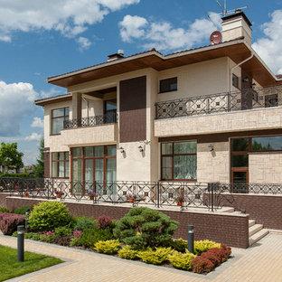 На фото: большой, двухэтажный фасад частного дома бежевого цвета в стиле современная классика с
