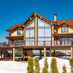 Пример оригинального дизайна: трехэтажный, бежевый частный загородный дом в современном стиле с двускатной крышей и металлической крышей
