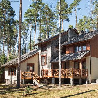 На фото: трехэтажный, коричневый частный загородный дом в стиле рустика с двускатной крышей, комбинированной облицовкой и крышей из гибкой черепицы с