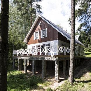 Modelo de fachada blanca, escandinava, de tamaño medio, de dos plantas, con revestimientos combinados y tejado a dos aguas