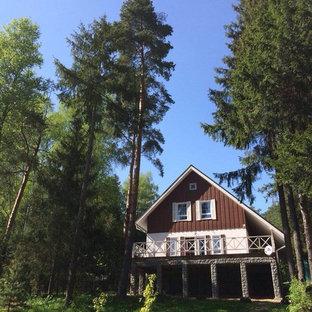 Ejemplo de fachada blanca, nórdica, de tamaño medio, de dos plantas, con revestimientos combinados y tejado a dos aguas