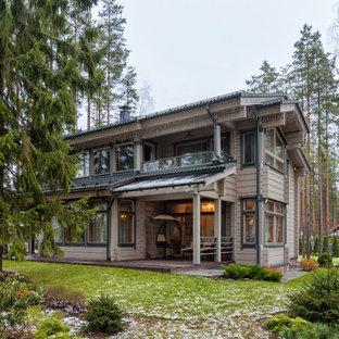 На фото: двухэтажный фасад частного дома коричневого цвета в стиле рустика с облицовкой из дерева, двускатной крышей и черепичной крышей с