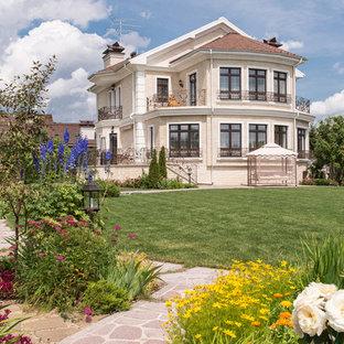 Удачное сочетание для дизайна помещения: большой, трехэтажный фасад дома бежевого цвета в классическом стиле с облицовкой из кирпича и двускатной крышей - самое интересное для вас