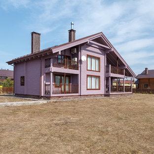 На фото: большой, двухэтажный, деревянный, фиолетовый частный загородный дом с двускатной крышей и металлической крышей с