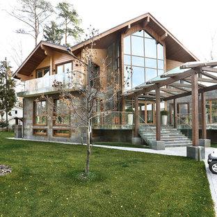 Новые идеи обустройства дома: большой, двухэтажный фасад дома коричневого цвета в современном стиле с облицовкой из дерева и двускатной крышей