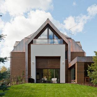 На фото: большой, двухэтажный частный загородный дом в современном стиле с комбинированной облицовкой и мансардной крышей