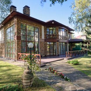 На фото: большой, двухэтажный, коричневый частный загородный дом в стиле рустика с облицовкой из камня и вальмовой крышей