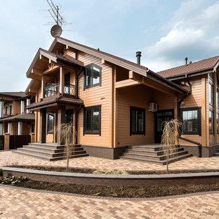 Свежая идея для дизайна: двухэтажный фасад дома среднего размера коричневого цвета в скандинавском стиле с облицовкой из дерева и двускатной крышей - отличное фото интерьера