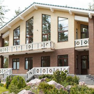 Modelo de fachada de casa beige, escandinava, grande, de dos plantas, con revestimiento de ladrillo y tejado a dos aguas