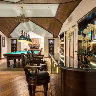 Пример оригинального дизайна интерьера: огромный п-образный домашний бар в стиле кантри с барной стойкой, темными деревянными фасадами, мраморной столешницей, коричневым фартуком, фартуком из дерева, паркетным полом среднего тона, фасадами с утопленной филенкой и коричневым полом