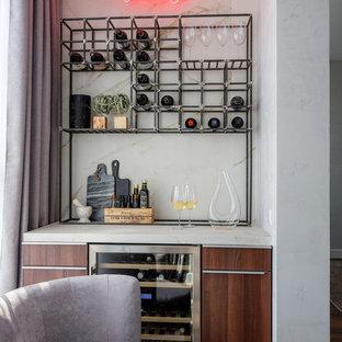 Удачное сочетание для дизайна помещения: линейный домашний бар среднего размера в современном стиле с плоскими фасадами, фасадами цвета дерева среднего тона и белой столешницей - самое интересное для вас