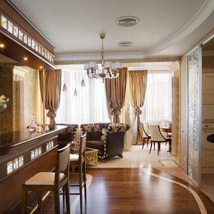 На фото: большой угловой домашний бар в классическом стиле с барной стойкой, фасадами с декоративным кантом, темными деревянными фасадами, гранитной столешницей, паркетным полом среднего тона и коричневым полом с