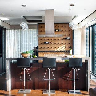 Свежая идея для дизайна: угловой домашний бар в современном стиле с барной стойкой, плоскими фасадами, темными деревянными фасадами, коричневым фартуком, фартуком из дерева, паркетным полом среднего тона, коричневым полом и серой столешницей - отличное фото интерьера