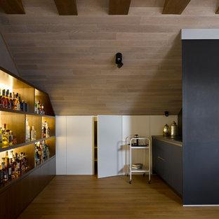 На фото: линейный мини-бар с мойкой среднего размера в современном стиле с плоскими фасадами, черными фасадами, черным фартуком, паркетным полом среднего тона, бежевым полом и серой столешницей с