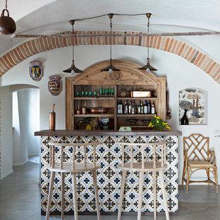 Idee per un bancone bar in campagna di medie dimensioni con ante in legno scuro, top in legno, pavimento con piastrelle in ceramica, pavimento grigio e top marrone
