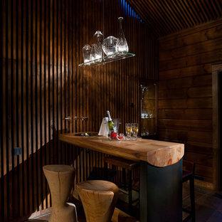 Пример оригинального дизайна интерьера: домашний бар в стиле рустика с барной стойкой, столешницей из дерева и коричневой столешницей