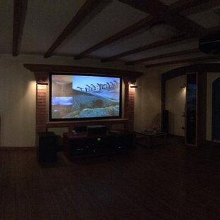 Immagine di un home theatre tradizionale di medie dimensioni e aperto con pareti gialle, pavimento in legno verniciato, schermo di proiezione e pavimento marrone