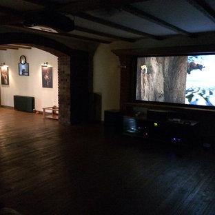 Esempio di un home theatre chic di medie dimensioni e aperto con pareti gialle, pavimento in legno verniciato, schermo di proiezione e pavimento marrone
