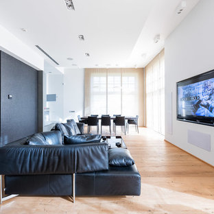 This is an example of a large contemporary open concept home theatre in Moscow with white walls, painted wood floors and a wall-mounted tv.