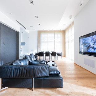 На фото: большой открытый домашний кинотеатр в современном стиле с белыми стенами, деревянным полом и телевизором на стене с
