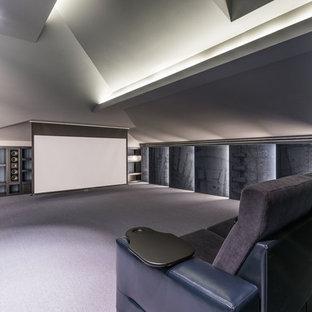 Пример оригинального дизайна: большой изолированный домашний кинотеатр в современном стиле с синими стенами, ковровым покрытием, проектором и серым полом